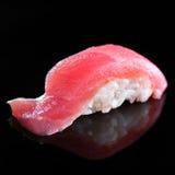 Enkelt stycke av tonfisksushinigiri på svart bakgrund Fotografering för Bildbyråer