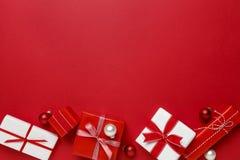 Enkla moderna gåvagåvor för röd & vit jul på röd bakgrund Festlig feriegräns Royaltyfri Foto