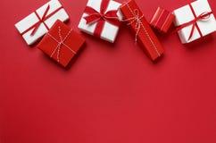 Enkla moderna gåvagåvor för röd & vit jul på röd bakgrund Festlig feriegräns Arkivbild