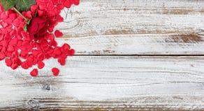 Enkla röda ros- och hjärtaformer som vilar på lantligt vitt trä Arkivbilder