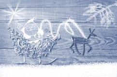 Enkla symboler av den faderChristmas släden som är ordnad från sågspån och renen som göras från torra träpinnar på trägrå bakgrun Royaltyfri Foto