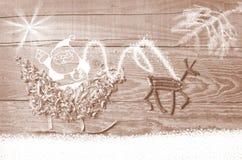 Enkla symboler av den faderChristmas släden som är ordnad från sågspån och renen som göras från torra träpinnar på trägrå bakgrun Fotografering för Bildbyråer
