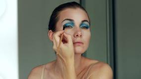Enlèvement de son maquillage Belle jeune femme gaie employant la brosse et regardant sa réflexion dans le miroir banque de vidéos