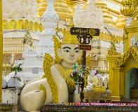 Enlejon skulptur och en Buddhastaty på den Shwedagon pagoden Arkivbilder