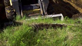 Enlever la couche de sol herbeux par le seau de bouteur pendant les travaux de la terre banque de vidéos