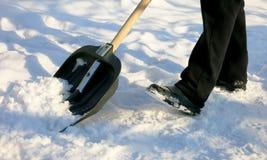 Enlever la neige avec une pelle après des chutes de neige Images libres de droits