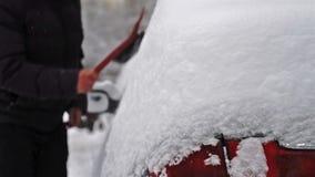Enlever la neige de la voiture après de grandes chutes de neige banque de vidéos