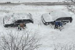Enlever la neige des voitures Photographie stock libre de droits