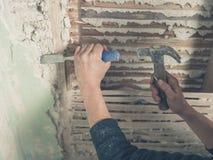 Enlever le plâtre avec le marteau Image libre de droits