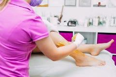 Enlever les cheveux inutiles sur les jambes Sucrage dans un salon de beaut? d?pilatoire images stock
