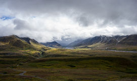 Enlighten Denali. Light shining on mountain through cloud in Denali National Park stock photo