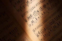 Enlighten the music. Grunge music notes with just center visible lightened by a ray of light Royalty Free Stock Photos