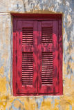 Enlightened window with red shutter Stock Image