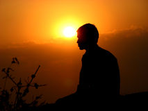 Enlightenment. An Indian meditating at sunset royalty free stock photo