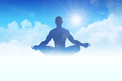 Enlightenment. Silhouette of a man figure meditating on clouds Stock Images