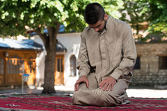 Enlightenment. Young Muslim Man Making Traditional Prayer To God While Wearing A Traditional Cap Dishdasha Royalty Free Stock Photos
