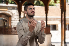 Enlightenment. Young Muslim Man Making Traditional Prayer To God While Wearing A Traditional Cap Dishdasha Royalty Free Stock Images