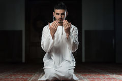 Enlightment. Young Muslim Man Making Traditional Prayer To God While Wearing A Traditional Cap Dishdasha Stock Photo