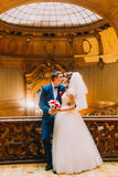Enloved groom kissing his charming bride near old wooden stairs with the background of luxury interior Stock Image