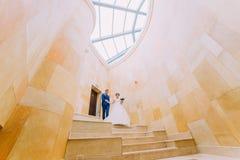 Enloved nygift personpar på marmortrappa med sandstenväggar på bakgrund Låg vinkel Fotografering för Bildbyråer