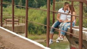 Enloved sinnliga par som kysser, medan sitta på bron på sommartid stock video