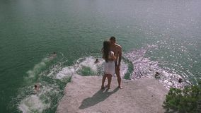 Enloved teenager couple kissing on a large stone near water surface with other young people jumping and bathing. Slow stock video
