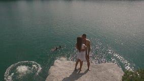Enloved tonåringpar som kysser på ett near vatten för stor stenblock, ytbehandlar med andra ungdomarsom hoppar och badar långsamt stock video