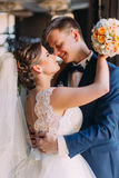 Enloved wedding couple. Beautiful bride with bouquet and handsome groom standing indoors, agaist window. Husband kissing Stock Photo