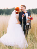 Enloved wedding couple enjoy a moment of happiness and lovingly look at each other on wheat field Stock Images