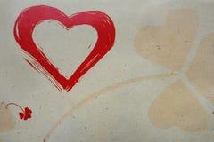 Enmålad ljus röd älska hjärta och en genomskinlig trefoilväxt av släktet Trifolium, ett symbol av lycka, på buse utföra i relief  Arkivfoton