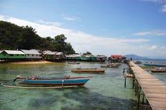 Embarcadero de la ciudad de la madera con los barcos Indonesia del jukung Foto de archivo libre de regalías