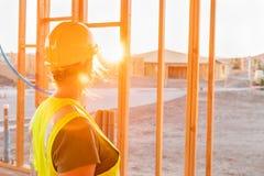 Enmarcar casero femenino de Looking Out From del trabajador de construcción el nuevo fotografía de archivo