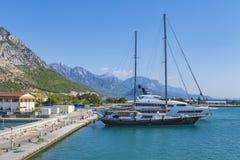 Enmasted yacht och ett vitt fartyg som parkeras på kajen, förtöjer, mot bakgrunden av portbyggnader, grön vegetation royaltyfri fotografi