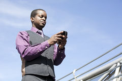 Ennegrezca al hombre de negocios que trabaja con el teléfono elegante Fotos de archivo