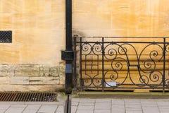 Ennegrezca el drenaje pintado de la lluvia en la pared de piedra de la arena con hierro labrado Fotos de archivo