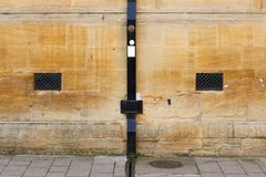 Ennegrezca el drenaje pintado de la lluvia en la pared de piedra de la arena con la ventilación Imágenes de archivo libres de regalías