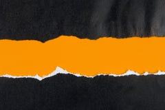 Ennegrezca el papel rasgado, espacio anaranjado para la copia Imágenes de archivo libres de regalías