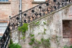 Ennegrezca la barandilla forjada y las escaleras de piedra de un pórtico Imágenes de archivo libres de regalías