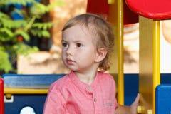 Ennegrezca a los niños observados que juegan el patio exterior, niño peculiar en el parque, niñez feliz Fotos de archivo libres de regalías