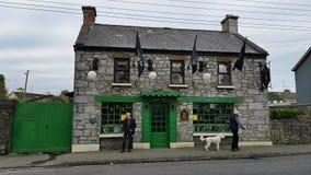 Ennis, Ierland - 17 Nov., 2017: Oude mens buiten een landelijke Ierse traditionele Bar in Provincie Clare, Ierland stock video
