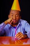 Ennuyé regardant l'homme utilisant la chemise bleue et le chapeau se reposant par la table tenant un burning simple de bougie, pa Image libre de droits