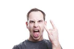 Enojado el hombre joven grita y muestra la muestra de la mano del rock-and-roll fotos de archivo