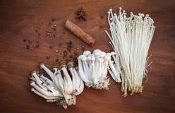 Enoki или золотой гриб Shimeji гриба иглы с травами и специями на деревянной предпосылке стоковые фотографии rf