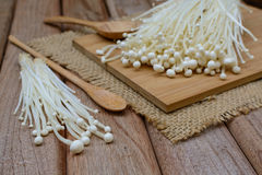 Enoki mushroom with spoon on wooden table Stock Photos