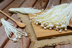 Enoki mushroom with spoon on wooden table Royalty Free Stock Photo