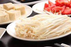Enokitake mushroom with tofu and sliced tomato on white plate Stock Photo