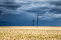 Enorm åskmoln över ett vetefält och elkraftpyloner Arkivfoto