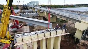 Enorm aktiv konstruktion med kranar som wokar män bredvid bron över floden arkivfilmer