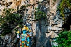 Enorm blå staty av den hinduiska gudhanumanen på ingången av batugrottor under molnig dag i Kuala Lumpur Malaysia Arkivfoton