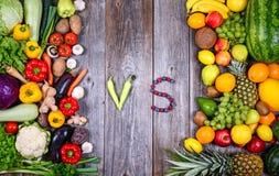 Enorm grupp av nya gr?nsaker och frukt p? tr?bakgrund - gr?nsaker VS frukt - h?gkvalitativt studioskott royaltyfria foton